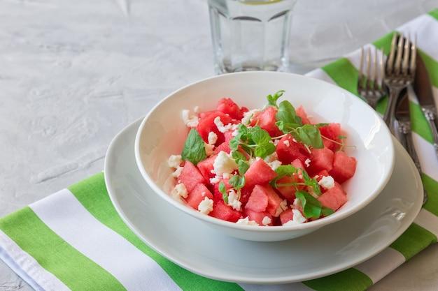 Frischer bio-salat mit wassermelone, feta-käse und minze auf hellgrauem betontisch. gesundes vegetarisches essen.