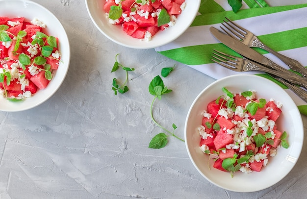 Frischer bio-salat mit wassermelone, feta-käse und minze in schalen auf hellgrauer betonoberfläche. gesundes vegetarisches essen. draufsicht.