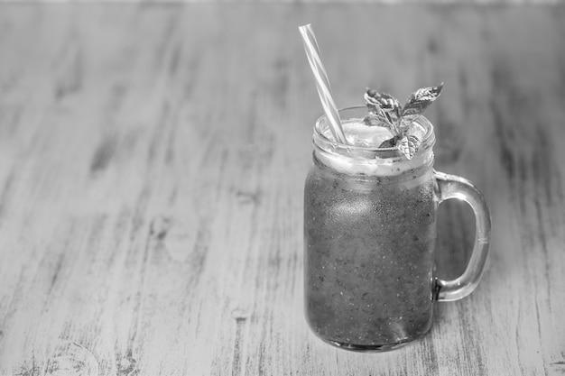 Frischer bio-smoothie im glasbecher auf holztisch, nahaufnahme. erfrischendes sommerliches fruchtgetränk. das konzept der gesunden ernährung. platz kopieren, schwarz und weiß