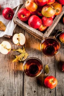 Frischer biohofapfelsaft in den gläsern mit den rohen ganzen und geschnittenen roten äpfeln, auf altem rustikalem holztisch, draufsicht copyspace