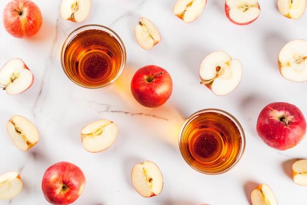 Frischer biohofapfelsaft in den gläsern mit den rohen ganzen und geschnittenen roten äpfeln, auf weißer marmortabelle, draufsicht copyspace