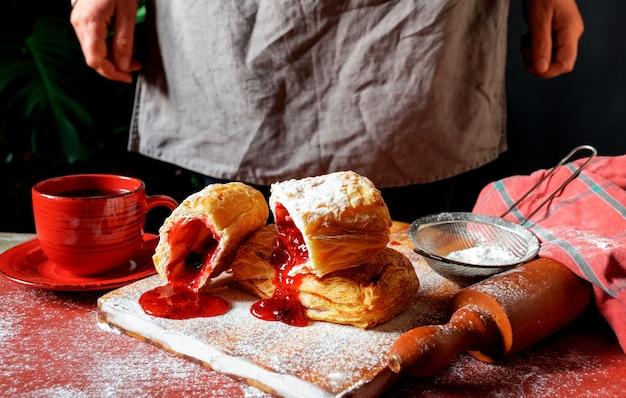 Frischer blätterteig besetzt mit pflaumen- oder johannisbeermarmelade auf dem tisch mit einer roten tasse und einem glas marmelade auf dem schwarzen hintergrund.