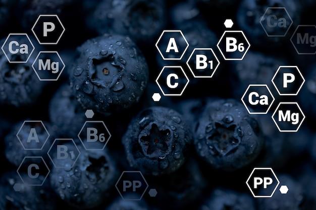 Frischer blaubeerhintergrund mit buchstabenbezeichnungen von vitaminen und mineralien gesundes essen veganes und vegetarisches konzept