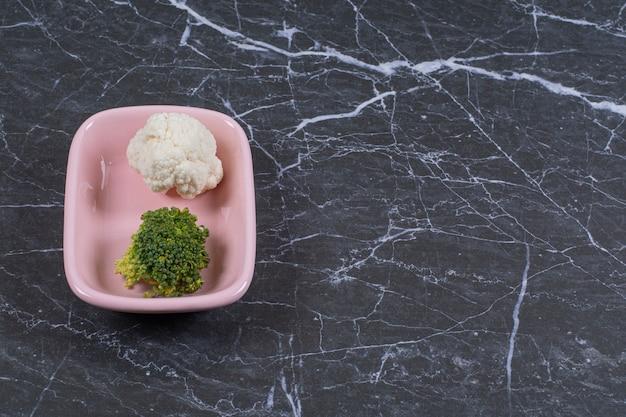 Frischer blumenkohl und brokkoli in der rosa schüssel über schwarzem stein.