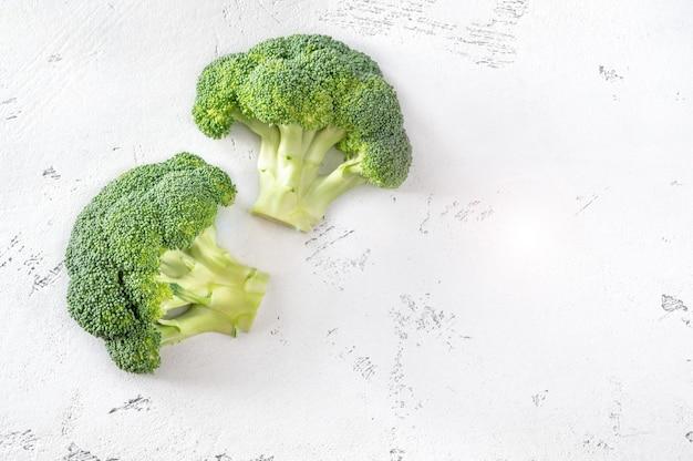 Frischer brokkoli auf dem weißen hölzernen hintergrund