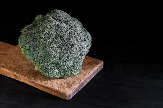 Frischer brokkoli auf einem schneidebrett auf einer schwarzen tabelle, rustikale art, dunkler schlüssel. gesundes essen