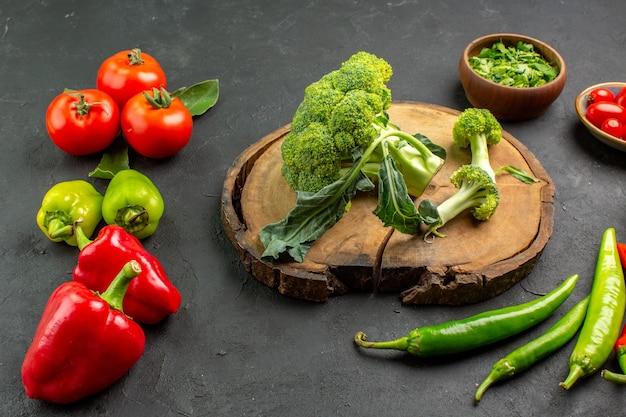 Frischer brokkoli der vorderansicht mit tomaten und paprika auf dunklem hintergrund
