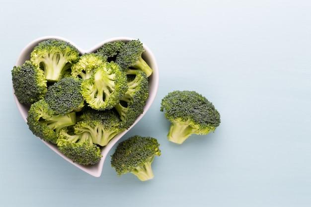 Frischer brokkoli in einer herzförmigen schüssel auf einem hölzernen hintergrund.
