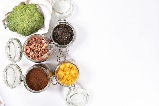 Frischer brokkoli in einer umweltfreundlichen beigen einkaufstasche auf weißer wand. gläser mit grünem tee, müsli, kaffee, nudeln. kein abfallkonzept.