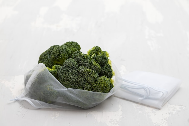 Frischer brokkoli mit mehrwegbeutel auf grau