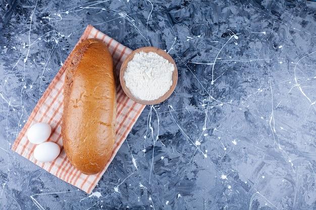 Frischer brotlaib mit zwei weißen hühnereiern und einer holzschale mehl auf einer tischdecke.