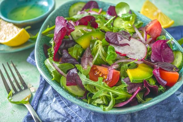 Frischer bunter frühlingssalat - avocado, frisches gemüse, salatblätter und feta-käse, hellgrüner betonhintergrund