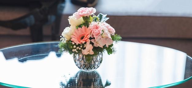 Frischer bunter romantischer pastellblumenblumenstrauß auf leerem glastabellenhintergrund