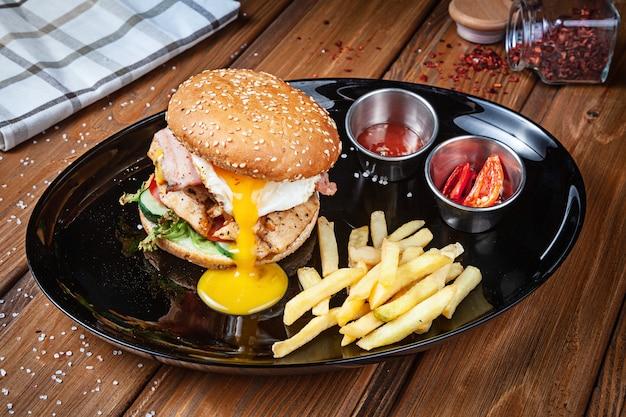 Frischer burger mit hühnerei, salat und sauce auf einem schwarzen teller mit pommes frites. amerikanisches fast food. chickenburger mit kopienraum auf hölzernem hintergrund. nahaufnahme, selektiver fokus. essen. grillmenü