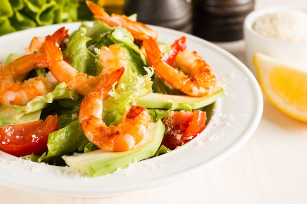 Frischer caesar-garnelensalat mit köstlichen garnelen, ruccola, spinat, kohl, arugula, ei, parmesankäse und kirschtomate gesund und diätlebensmittelkonzept.