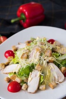 Frischer caesar salad mit huhn auf einer weißen platte auf dunklem stein.