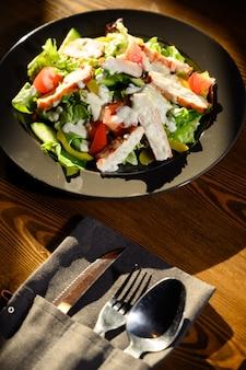 Frischer caesar-salat im schwarzblech auf dunklem holztisch. ansicht von oben.