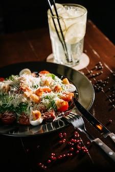 Frischer caesar-salat in der weißen platte auf dunklem holztisch. draufsichtkopienraum.