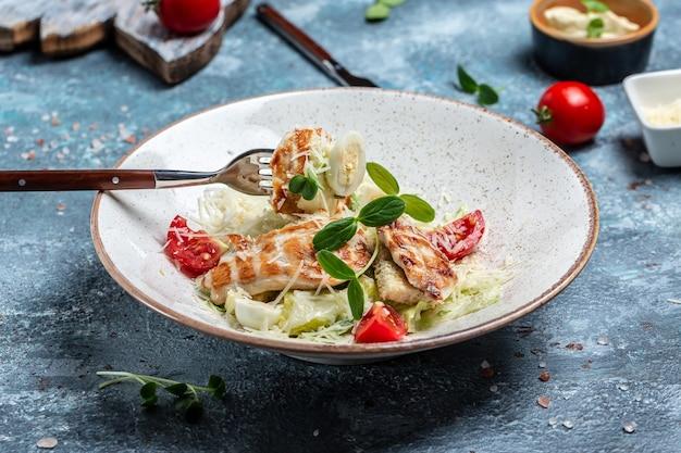 Frischer caesar-salat mit gegrilltem huhn, käse und croutons, wachteleiern und kirschtomaten. köstliches ausgewogenes lebensmittelkonzept. ansicht von oben.