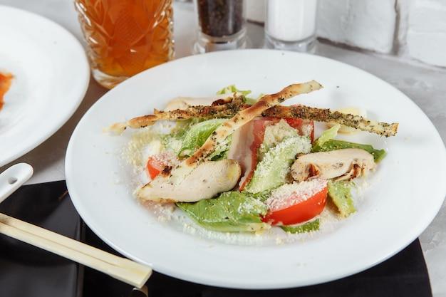 Frischer caesar-salat mit hühnerbrust und tomaten