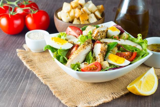 Frischer caesar-salat mit köstlicher hühnerbrust, ruccola, spinat, kohl, rucola, ei, parmesan und kirschtomate auf hölzernem hintergrund. öl, salz und pfeffer. gesundes und diät-lebensmittelkonzept.