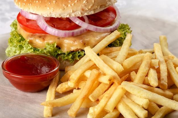 Frischer cheeseburger mit pommes frites und tomatensauce