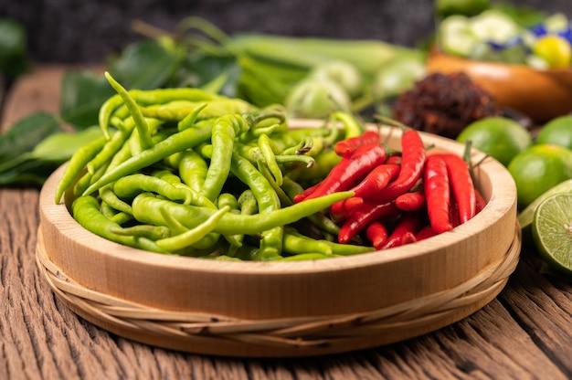 Frischer chili auf einem holztablett mit zitronen-kaffir-limettenblättern.
