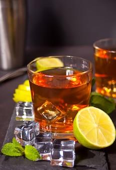 Frischer cocktail cuba libre mit braunem rum, cola, minze und limette auf schwarzem hintergrund. long island eistee cocktail.