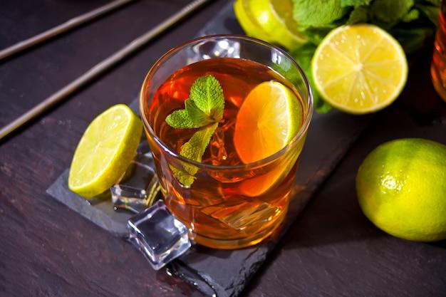 Frischer cocktail cuba libre mit braunem rum, cola, minze und limette auf schwarzem tisch. long island eistee cocktail.