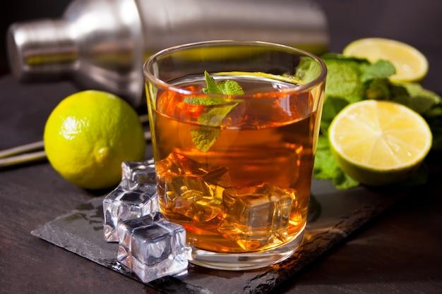 Frischer cocktail cuba libre mit braunem rum, cola, minze und limette auf schwarzer oberfläche. long island eistee cocktail.