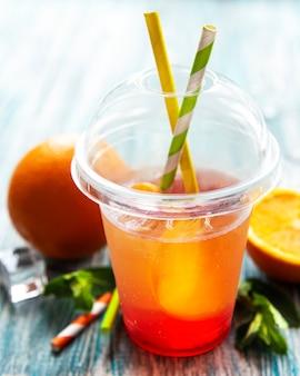Frischer cocktail mit orange und eis. alkoholisches, alkoholfreies getränk auf einer blauen holzoberfläche