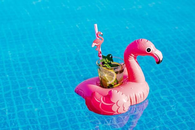 Frischer coctail mojito auf aufblasbarem rosa flamingospielzeug am schwimmbad. urlaubskonzept.