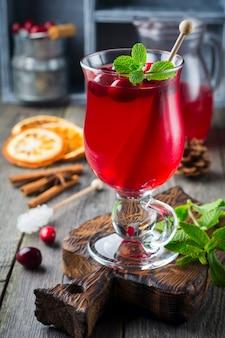 Frischer cranberrysaft mit zimt und anis in gläsern auf der alten holzoberfläche. selektiver fokus.