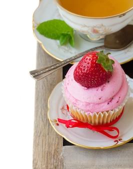 Frischer cupcake mit roter erdbeere im teller und tasse minztee lokalisiert auf weißem hintergrund