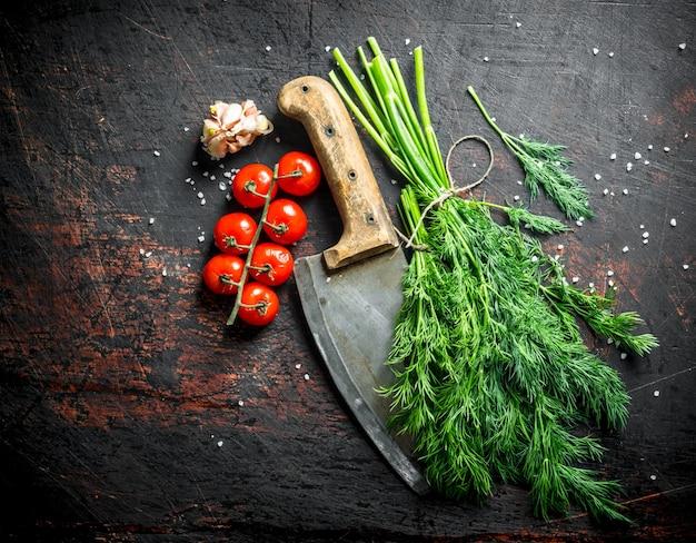 Frischer dill mit messer, tomaten und knoblauchzehen auf schwarzem rustikalem tisch