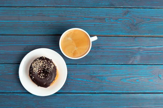 Frischer donut mit kaffee auf holzoberfläche, draufsicht