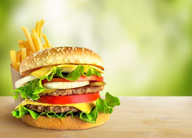 Frischer doppelter hamburger und pommes frites auf grünem naturhintergrund