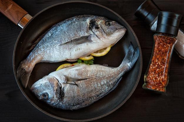 Frischer dorado-fisch gefüllt mit zitrone und gewürzen auf dem teppich. meeresprodukte, kochen.