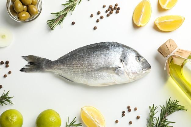 Frischer dorado-fisch, gewürze und kochzutaten auf weiß