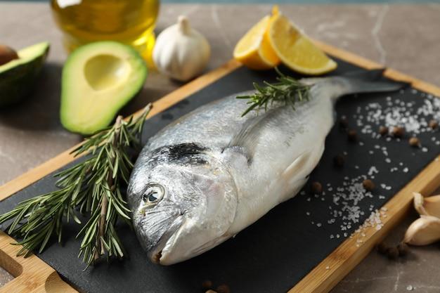 Frischer dorado-fisch und kochende bestandteile auf grauem hintergrund, nahaufnahme