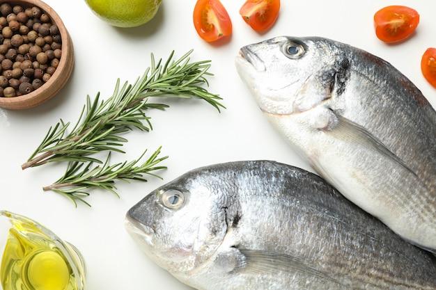 Frischer dorado fischt und kocht bestandteile auf weißem hintergrund, draufsicht