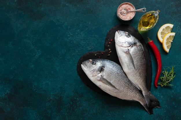 Frischer doratofisch, gewürze und olivenöl auf steinschneidebrett auf dunkler tabelle. draufsicht, raum kopieren.