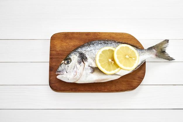 Frischer doratofisch mit zitrone auf hölzernem schneidebrett auf weißem holztisch. draufsicht, raum kopieren