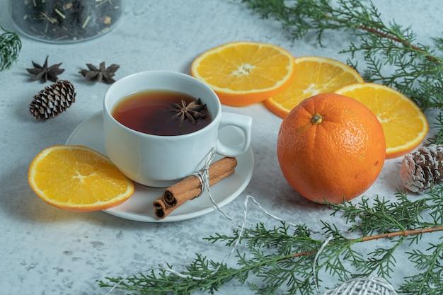 Frischer duftender tee mit bio-orange auf weihnachtstisch.