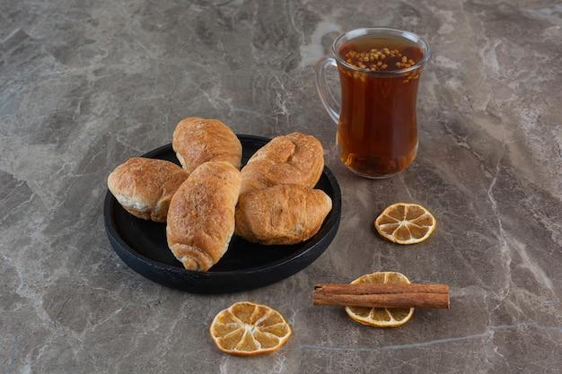 Frischer duftender tee mit hausgemachten keksen auf grau.