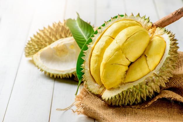 Frischer durian oder durio zibthinus murray auf sack und altem holzhintergrund, könig der frucht von thailand auf sommersaison
