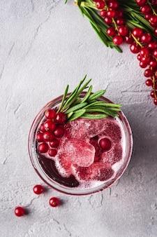 Frischer eiskalter fruchtcocktail im glas, erfrischendes sommerbeerengetränk der roten johannisbeere mit rosmarinblatt auf steinbetontisch, draufsicht