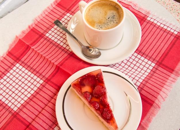 Frischer erdbeerkäsekuchen und eine tasse kaffee mit einem löffel auf einer untertasse, eine draufsicht auf ein süßes dessert mit erdbeerbeeren in gelee, das konzept eines köstlichen gourmetfrühstücks.