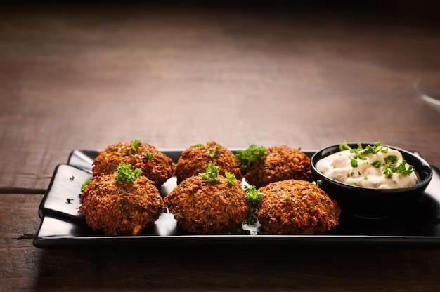 Frischer falafel mit petersilie und tzatziki soße im schwarzblech auf holztisch.
