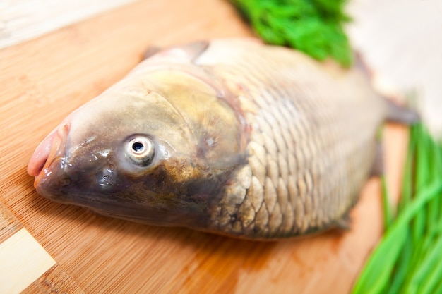 Frischer fisch auf einem küchenbrett mit gemüse.